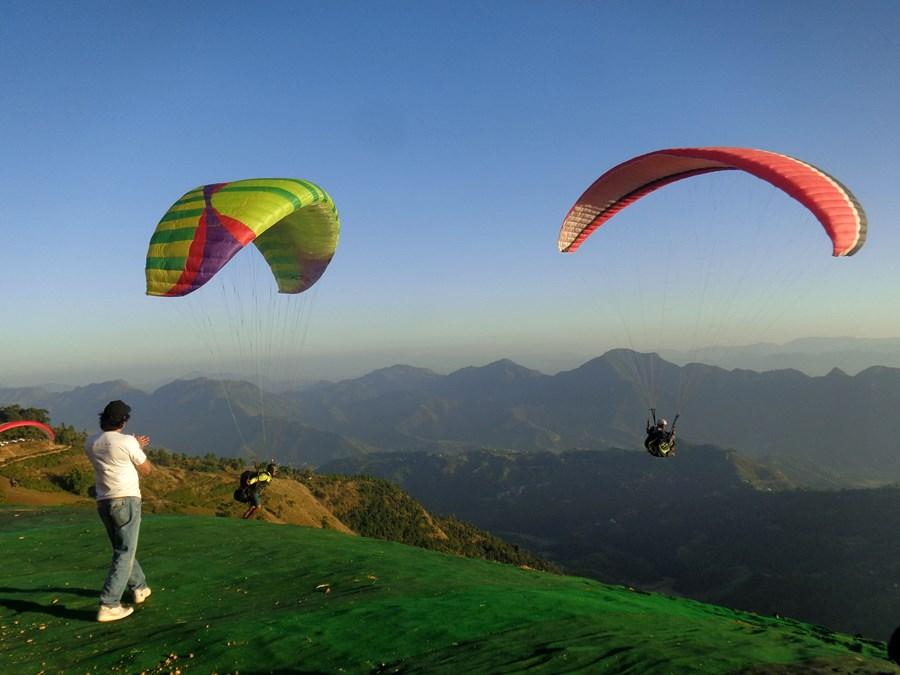 स्याङजाको पर्यटकीयस्थल स्वरेकमा आइतबार प्याराग्लाइडिङ गर्दै पर्यटक । तस्वीर : वासुदेव पौडेल, रासस