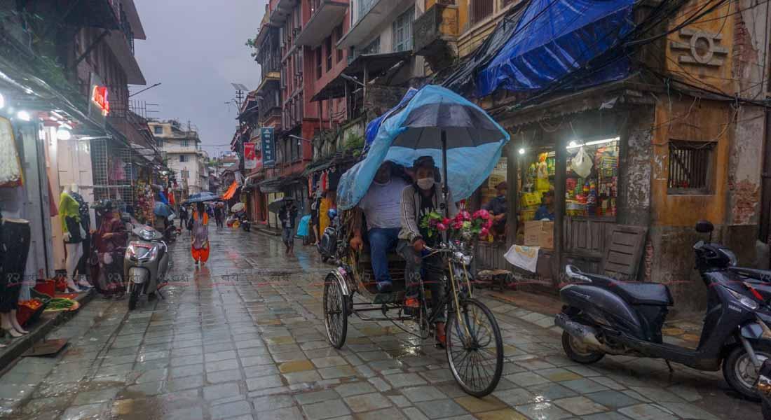 बिहीबार साँझ पानी परिरहेको बेला काठमाडौको मरु टोलबाट आफ्नो ग्राहकलाई रिक्सामा गन्तव्यमा लग्दै रिक्साचालक । तस्बिरः सुनिल प्रधान