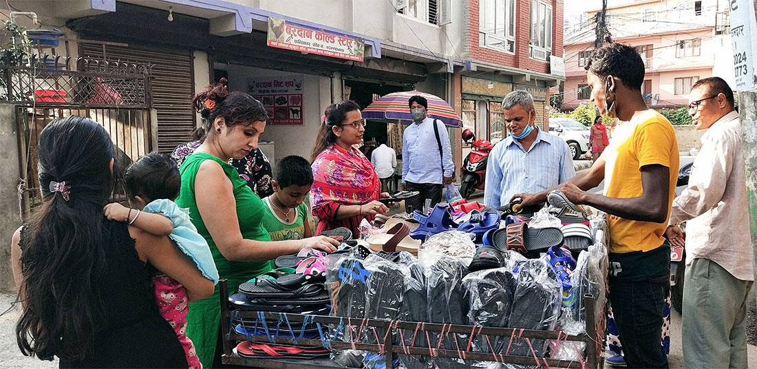 ठेलामा व्यापार : काठमाडौंको नयाँ बानेश्वरस्थिति मिलिजुली चोकमा ठेलामा जुत्ता-चप्पलको कारोबार गर्दै ग्राहक र व्यापारी । तस्बिर : बाह्रखरी