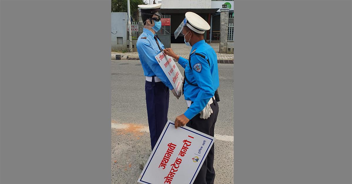 काठमाडौंका सडकमा रहेको डमी ट्राफिकको हातमा सूचना बोर्ड राख्दै एक ट्राफिक प्रहरी । तस्बिरः बाह्रखरी
