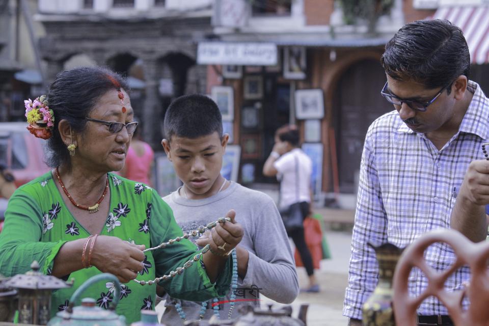 ललितपुरको पाटन दरबार स्क्वायर परिसरभित्र पर्यटकलाई सामान बेच्दै व्यापारी । तस्विर : सरिता खड्का