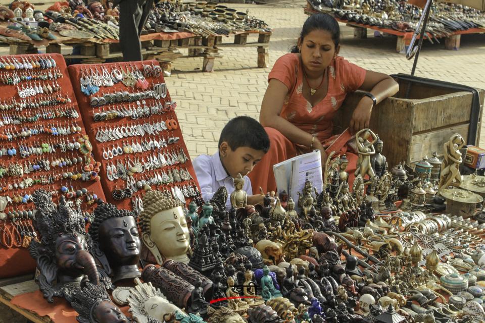 काठमाडौंको बसन्तुरमा स्कुलबाट फर्किएपछि आमाको फुटपाथ पसलमा 'होमर्वक' गर्दै एक बालक । तस्बिरः सरिता खड्का